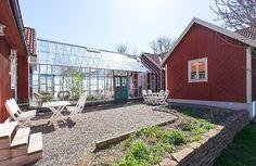 Sweden, Öland. Greenhouse linking two buildings. Vintage doors.