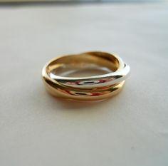 Algunos lo llaman el anillo de la Trinidad... algunos lo llaman el anillo de balanceo... Siempre lo he llamado el trío.  Tres anillos entrelazados en una sola. Las bandas parecen rodar sobre el dedo. Me gusta mejor cuando que combinan oro y plata en un anillo, porque el contraste es realmente impresionante.  Hecho del alambre de 2 filamentos 2,5 mm ancho 14k oro lleno y 1 hebra de alambre de 2,5 mm ancho sólido.925 plata esterlina. Por supuesto si lo prefiere que puede tener oro esterlina 1…