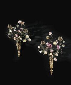 <b>PAIRE D'APPLIQUES DE STYLE LOUIS XV</b>  <br /> En bronze ciselé et doré, fleurs en porcelaine tendre du XXe siècle, à deux bras de lumière <br /> H. : 34 et 38 cm <br /> l. : 21,5 et 24 cm <br />  <br /> A pair of Louis XV style ormolu-mounted and soft-paste porcelain two-branch wall-lights <br />  <br /> <br />  <br />  <br />