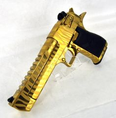 "Magnum Research Desert Eagle Mark XIX .50 A.E. Gold Bengal Tiger 6"" *NIB*. DE50TG-TS. The Desert Eagle Pistol has emerged as a pop-culture icon. This gas-operated, rotating bolt semi-automatic pistol is precision-cast and machined from high-quality carbon steel. Features a picatinny rail, ambidextrous safety, & is anatomically designed for two-hand shooting. Titanium Gold w/ Bengal Tiger Stripe finish. 7+1 capacity of .50 A.E. 6"" barrel. 71.4 oz. $2399.99"