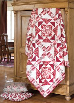 This traditional quilt, Touch of Rouge, features a variety of red and tan prints. This traditional quilt features a variety of red and tan prints.