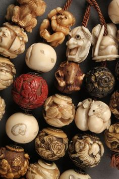 DETAIL VIEW: Collection of 26 Asian ojime beads,carved from ivory, bone, celluloid, cinnabar strung on a tassel depicting a tiger, skull, devil faces, rats, flying crane, butterfly. | These were all collected by George and Charles Mitchell during the course of several trips to China and Japan in the late 19th century.