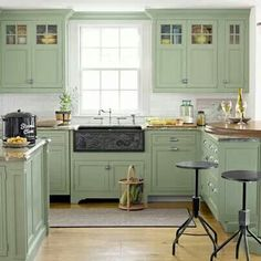 What a pleasing country kitchen design. The sage green kitchen cabinets are a beautiful color. And don't miss the custom-carved apron-front sink made of slate. Green Kitchen Cabinets, Kitchen Redo, New Kitchen, Kitchen Dining, Kitchen Ideas, Upper Cabinets, Colored Cabinets, Mint Kitchen, Pastel Kitchen