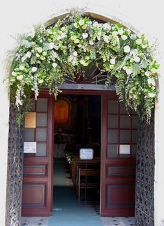Garland with white roses, white lisianthus and greenery.