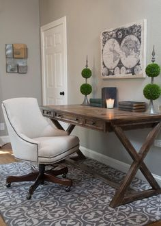 The new home office is staged with a traditional wood desk and white upholstered chair on top of a gray and white area rug. Topiaries, old books and a map set the mood for creative exploration, as seen on HGTV's Fixer Upper.