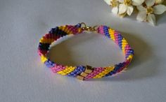 Neon friendship bracelet made with bright shocking pink, purple and yellow thread and featuring three golden focal cube beads, Great as a gift or just a great beach bracelet.    The bracelet fastens with a golden lobster clasp and measures 7.5 inches long but also has a stretch element so would easily stretch to fit a wrist up to 8,5 inches $16.00