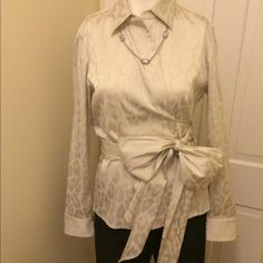 Beautiful Ann Taylor oyster color wrap blouse, S10 Blouse is in excellent condition and only worn a couple of times.  Wrap blouse is in beautiful oyster color with tone-on-tone animal print pattern in the fabric.  Large side tie bow.  Makes any outfit look on the dressier side.  Very stunning shirt that gets lots of attention and compliments!! Ann Taylor Tops Blouses