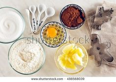 Ingredients for baking on a white marble table : flour, eggs, cocoa powder, sugar, butter and measuring spoons, molds