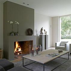 gemauerter-kamin-graue-wand-weiße-wand-graue-möbel-kerzendeko-grauer-plüschteppich-designer-couchtisch