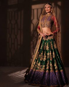 A handcrafted silk lehenga rendered in jewel tones of emerald,ruby and lapis lazuli, offset by delicate floral motifs inspired by Mughal…