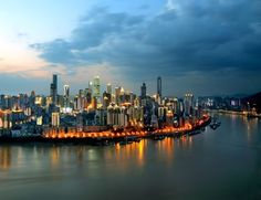 Skyline of Yuzhong Peninsula with skyscrapers and high-rise buildings at the juction of the Yangtze River and the Jialing River at sunset in Chongqing, China (AP Photo) China Today, Building Concept, 2nd City, Central City, High Rise Building, Futuristic Architecture, City Lights, Places Ive Been, The Good Place