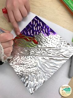 Students drawing on metal embossing using permanent markers.