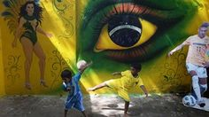 Young Indian children in Brazil (R) and Argentina football attire play in front of wall graffiti