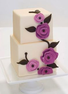 Simple white cake with purple flowers, great to make the flowers the wedding colors, make the cakes small, and serve one to each table. Maybe have the top tier be something like Italian creme cake and devils food cake on the bottom.