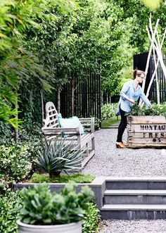 "The side gardens also play an important role in the story of this garden. On the north side are Lynn's all-important raised vegie gardens. Made from recycled apple crates and sourced from The Little Vegie Patch Co, these boxes are filled with herbs such as thyme, parsley, oregano, coriander and mint. ""We love being able to run outside and grab some herbs while we're cooking"""