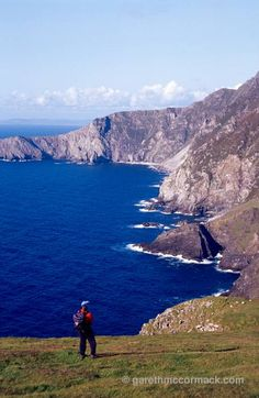 Walker beneath the cliffs of Croaghaun, Achill Island, Co Mayo, Ireland