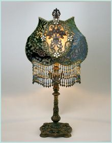 Detailed, ornate early 1900s metal lamp base holds a Cameo shade in tones of dark green midnight blue. Antique hand-dyed cut velvet, gold metallic lace and scroll trim overlay the panels and a pair of vintage rhinestone encrusted appliqués adorn the front and back. Hand beaded fringe pick up all the colors of the shade. A jeweled pull chain turns on the lamp. 28 inches high to the top of the finial.