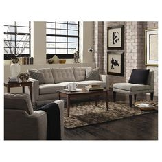 Gray sofa with a tufted back and two throw pillows. Made in the USA.   Product: SofaConstruction Material: Wood and fa...