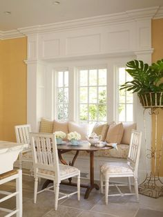 An antique oval table and white-painted chairs pull up to a built-in window seat.