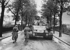 Soviet tank T-34-85, accompanied by infantry moving down the street on the outskirts of Berlin.