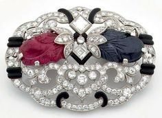 Pin Platinum set brilliant-cut diamonds and princess nets enhanced black enamel and set in the center of a sapp hire and a ruby engraved. Art Deco