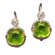 Peridot Diamond Gold Earrings by Marie E. Betteley. Based on Romanov era earrings from St. Petersburg, the vibrant green peridot drops recall fine Siberian specimens from 19th century Russia. Each is cushion-cut (an 18th century gem cutting style popularized by Catherine the Great) and set within a conforming bezel of 18k white gold. The gem is held by double prongs and surmounted by an antique-cut diamond. c 2005