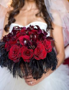 Such a cool bouquet of red bacara roses, burgundy mini callas, fiddlehead fern, and black ostrich feathers around the collar!