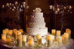 The four tier cake by The Cakewalk Shop is a centerpiece in itself, surrounded by rose petals, sparking, mirrored candelabras and illuminated by candlelight.
