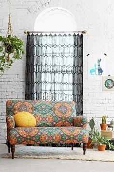 Só a ideia: parede de tijolinho, plantas, sofá colorido e cortina de crochê