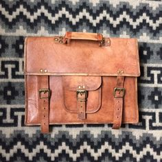 """Handmade leather messenger bag/ briefcase Handmade unisex Indian goat leather messenger bag. This bag is colored naturally by the sun followed by an oil finish, giving it a rustic vintage look.  Great for 13"""" or smaller laptop  Features a sturdy and durable canvas lining  Dimensions: 11""""H X 15""""L X 4""""W  *please acknowledge these are all handmade, so please only reasonable offers.  *Handmade in Udaipur, Rajasthan, India by a small group of friends-- Bags Laptop Bags"""