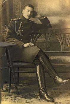 Postcard do Príncipe Constantino Constantinovich em 1911. Ele está sentado em um banco, de frente voltado em parte para a direita e, com as pernas cruzadas. O braço esquerdo está apoiado sobre a parte de trás do banco. Há uma mesa para a esquerda e uma pintura atrás.