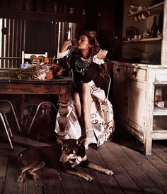Sitting in a kitchen, Chloe Lecareux wears a Gucci sweater, skirt and heels