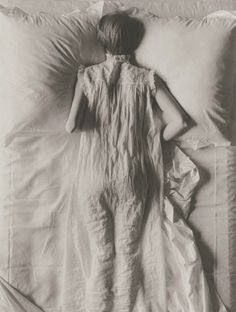 Grief, alone in bed, but looking longingly at empty space next to her , perhaps man lost at war. Hat/uniform/clothing/flower?
