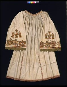 Dress Crete, Greece 1700s . Linen embroidered in silks, with bobbin lace.Dress of five widths of linen falling from a round gathered neck, the hem and the lower part of the seams decorated with coloured bobbin lace. Wide and exceptionally long sleeves fall from the gathers at the neck band. Gold lace and floral devices, embroidered in polychrome silks with three female figures, possibly a bride and her attendants.