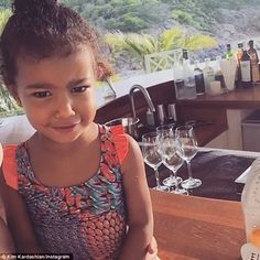 Summer style:North wears a playful bathing suit while her mother has her hair in braids and looks nearly makeup free