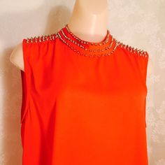 Coral top with studs on collar Amazing coral colored top . Shorter in front than back, chest is about 24 inches across(pit to pit---one way). Tops