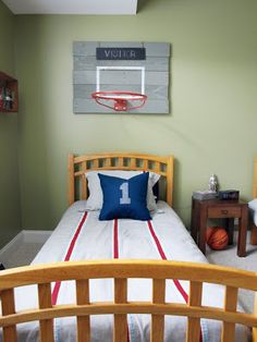 Vintage basketball rim mounted on chalkboard in a teenaged boy's room. The boy's  name is written on the chalkboard. Another bed and basketball rim are nearby for guests--the chalkboard enables the hosts to write the guest's name above the bed.