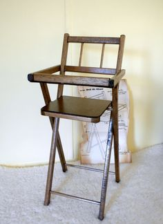 This is a 20 inch wooden walnut finish folding doll high chair in original packaging by Mapes Industries, Wellsville NY. It is unused and