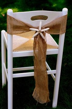Burlap tie around white wooden chairs...would be cute also with small pine branch & pine come, or other rustic/theme related trinket. #beachwedding