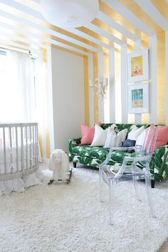 Lovely gold stripes make a big impact in the white nursery [Design: Fox Design Studio]