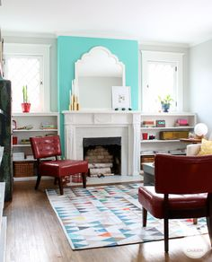 teal wall, vintage chairs, fireplace.
