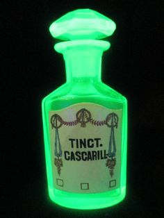 Vaseline glass apothecary bottle.  The label on the front is porcelain enameled and the stopper is octagonal faceted.