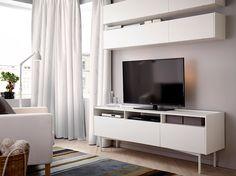 Woonkamer met wandkasten en tv-meubel, alles in het wit