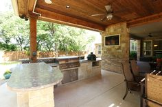 Spacious outdoor kitchen and dining area. Kitchen includes stainless BBQ, refrigerator, and green egg. By Outdoor Signature in Argyle, TX