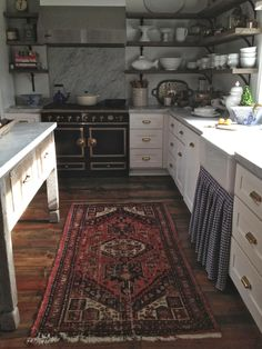 Vintage rug in the kitchen. Rustic open wood shelves. Old table as an island.