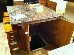 Hidden room beneath kitchen island. A twofer - gives needed kitchen use and conceals a room! Cool