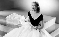 1954: American actress Grace Kelly on the set of Rear Window, directed and produced by British Alfred Hitchcock.