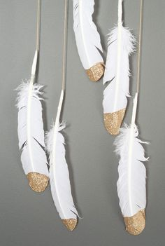 Gold-dipped feathers #DIY. Hang them as a mobile or string them for a garland. A must try!