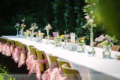 Prachtig gedecoreerde tafel met bloemen en tule strikken aan de stoelen voor het diner tijdens deze tuinbruiloft.