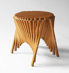 Rising side table, flexible made out of a flat piece of wood.